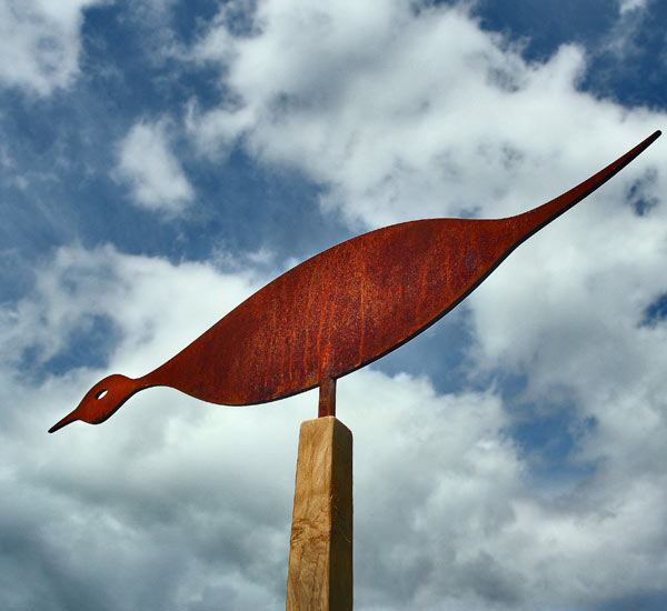 Curvaceous bird sculpture crafted from rusted metal for the garden